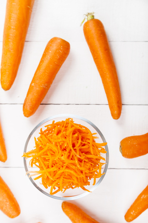 Grate  carrots in a bowl on a white wooden table, top view. Tasty and healthy food. Diet.