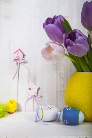 Bouquet purple tulips and Easter eggs on a light wooden background. Easter still life can be used as a postcard. Archivio Fotografico