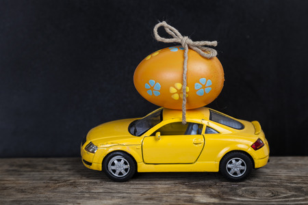 Yellow toy car with easter egg. Easter still life.