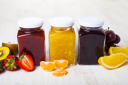 Three jars with jam on a wooden background. Delicious dessert and fresh fruits close-up.