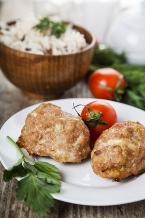 Delicious cutlets, rice, tomatoes and parsley  on the table. Dinner time. Stock Photo