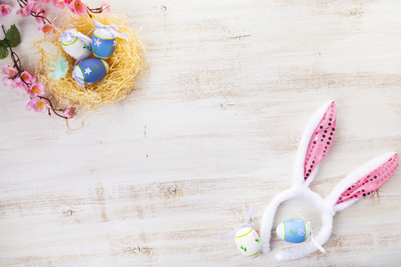 Easter eggs on wooden background. Easter still life with rabbit ears and eggs