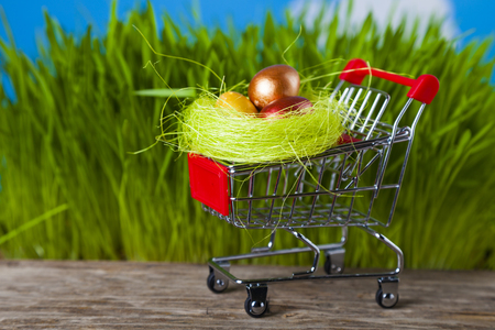 Shopping cart with Easter eggs on a background of green grass.  Easter sale. Stock Photo