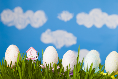 Easter still life with green grass and Easter eggs against the sky. Happy Easter. Easter greeting card.