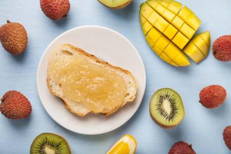 Jam of tropical fruits on bread on a wooden table. Delicious dessert for breakfast.