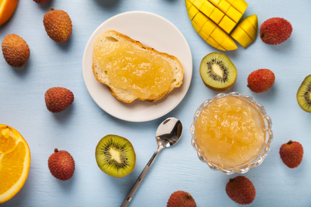 Jam of tropical fruits on a wooden table. Delicious dessert for breakfast.