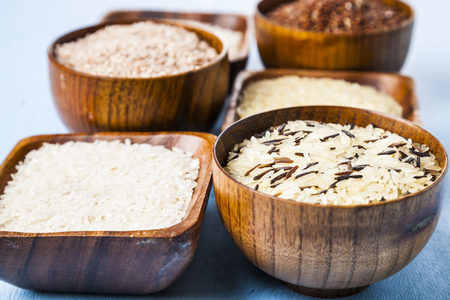 Six bowls with different varieties of rice on a wooden background. Ingredient for a healthy diet.
