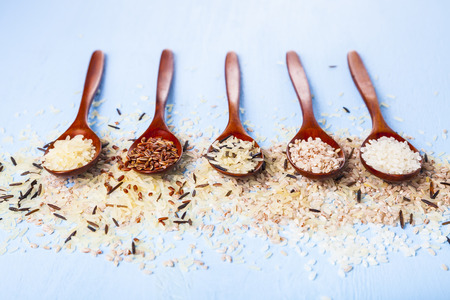 Five spoons with different grades of rice on an old wooden background. Ingredient for a healthy diet.