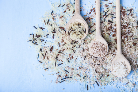 Three spoons with different grades of rice on an old wooden background. Ingredient for a healthy diet. Stock Photo