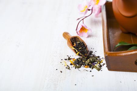Ceramic teapot, tea leaves and sakura on a wooden tray. Oriental tea.
