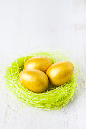 Golden eggs in a nest on a wooden background. Easter still life with nest and eggs.