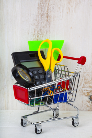 Items for school in a shopping cart on a wooden background. Concept of buying items for school. Back to school.