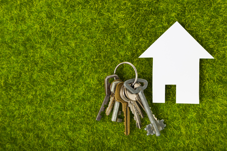 Cardboard house and keys on green grass. Purchase of suburban real estate.