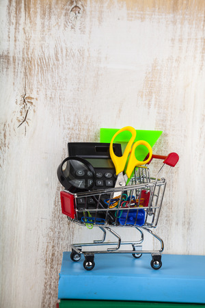 Items for school in a shopping trolley and books on a wooden background. Concept of buying items for school.
