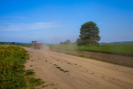Road near the potato field on a sunny summer day. Tractor travels in the distance. Agriculture, cultivation of vegetables. Stock Photo