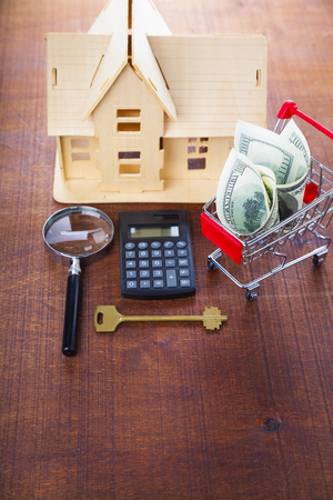 Money in a shop trolley,calculator, magnifier,key and a house on a wooden background.. Buying a property.