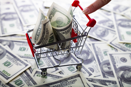 Shopping trolley with dollars and a womans hand. Sale. Stock Photo