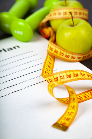 Apples,  diet plan and measuring tape on a wooden background. Concept of diet and healthy lifestyle.