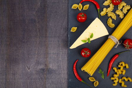 Different pasta and cheese on a dark wooden background. Raw pasta, chili, tomatoes and basil close-up.