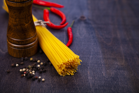 Spaghetti on a dark wooden background. Raw pasta, chili and pepper mill close-up. 免版税图像