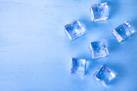 Ice cubes on a blue wooden background