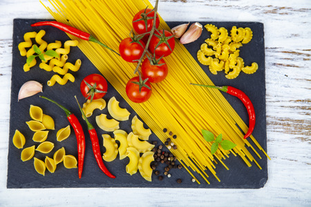 Different pasta on a wooden background. Raw pasta, chili, tomatoes and basil close-up. Reklamní fotografie