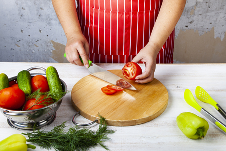Woman in a red apron is cutting vegetables for a salad on a table in the kitchen. Cooking. Archivio Fotografico