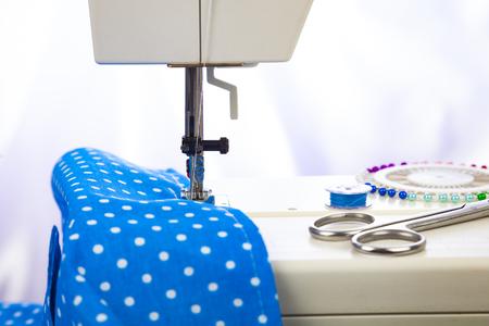 Maszyna do szycia i zbliżenie niebieskiej tkaniny