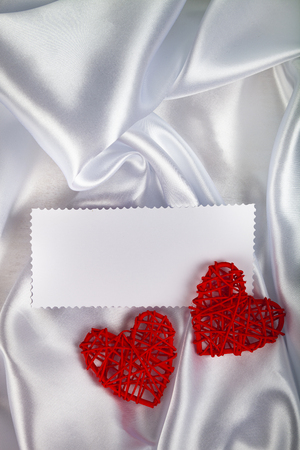 White silk fabric with folds, two red hearts and a note. Beautiful romantic background.