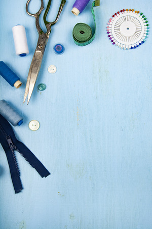 Sewing accessories on a blue wooden background. Measuring tape, pins, buttons, zipper, scissors and thread. Archivio Fotografico