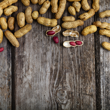 Peanuts on a wooden background. Delicious and healthy nuts close-up.  Place for your text.