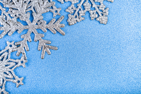 Silvery snowflakes on a blue shiny background. background. Christmas decor.