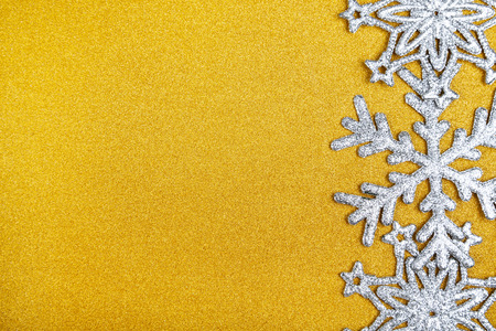 Silvery snowflakes on a yellow shiny background. background. Christmas decor.