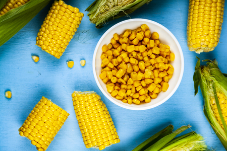 Ripe corn on a blue table close-up. Raw and canned corn in a white bowl.