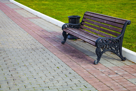 Bench, a stone walkway in the park  and green lawn. Beautiful summer city park for walking. Stock Photo
