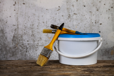 Items for home or office renovation against a gray wall. Paint can and brush on the table.