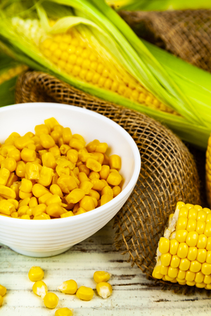Ripe corn on a wooden table close-up. Raw and canned corn in a white bowl. 写真素材