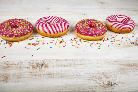 Pink donuts on a wooden background. Delicious dessert. 免版税图像