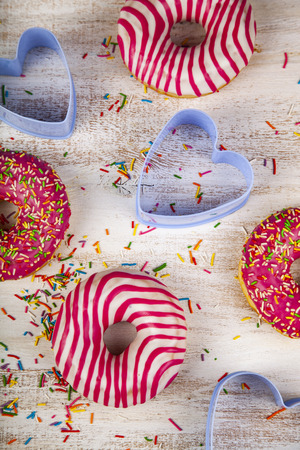 Donuts and blue hearts on a wooden background. Delicious dessert.