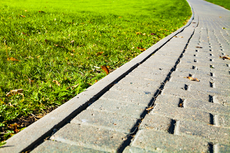 Stone path in the park and green lawn. Beautiful summer city park for walking. Imagens - 112491464