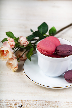 Berry macaroons in a white cup and rose on a wooden background. Tasty cookies.