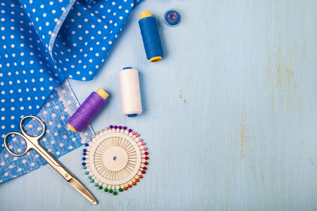 Sewing accessories on a blue wooden background. Blue fabric, scissors and thread.