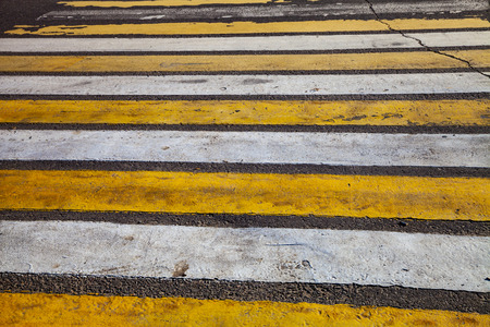 Pedestrian crossing with white and yellow stripes close-up.