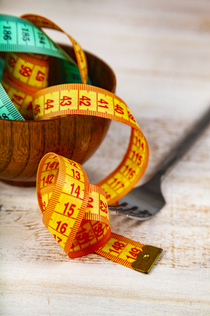 Measuring tape in a wooden bowl and fork. Concept of diet and weight loss. Stock Photo