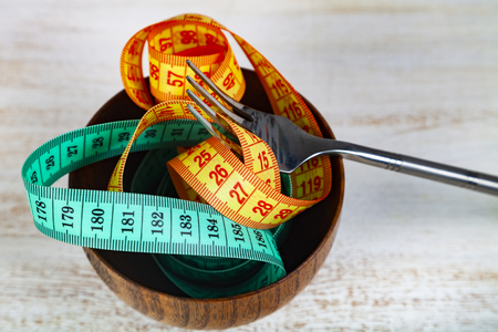 Measuring tape in a wooden bowl and fork. Concept of diet and weight loss. Archivio Fotografico