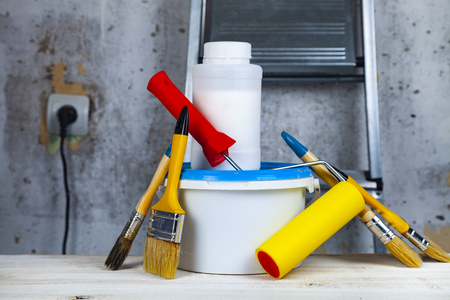 Paint can,roller and brush on the table. Items for home or office renovation against a gray wall and ladder. Reklamní fotografie