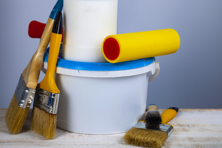 Paint can, roller and brush on the table. Items for home or office renovation on gray background.