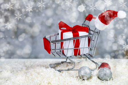 Christmas gift in a shopping cart on grunge background. Christmas sale.