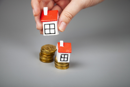 Small houses on the coins. Man takes one house by hand. Buying or selling real estate.