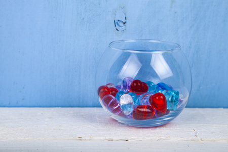 Multicolored glass hearts in a round vase on a blue background.